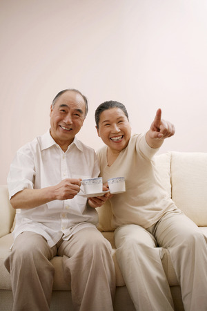 viendo television: Senior man and woman drinking coffee while watching television