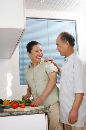 Senior woman cutting vegetables in the kitchen with senior man by the side