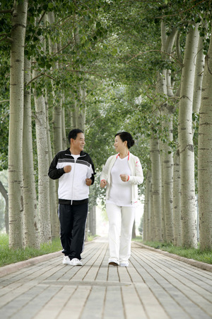 Senior man and woman jogging in the park