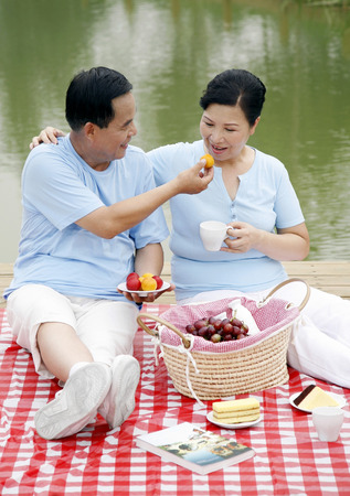 picnicking: Senior man and woman picnicking by the lakeside
