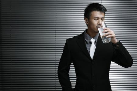 Geschäftsmann trinkt ein Glas Wasser