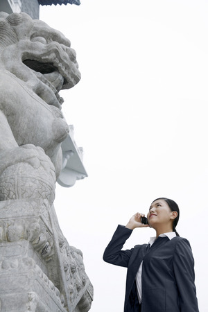 Businesswoman talking on her cellular phone, looking up at a lion statue LANG_EVOIMAGES