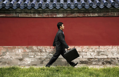 Businessman walking while carrying briefcase Stock Photo
