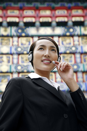 microphone headset: Businesswoman using microphone headset LANG_EVOIMAGES
