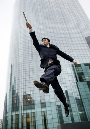 baton: Businessman jumping while holding baton