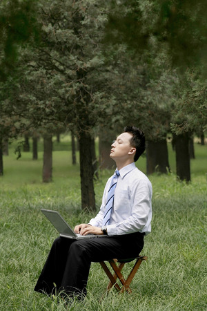eyes closing: Businessman closing his eyes while using laptop