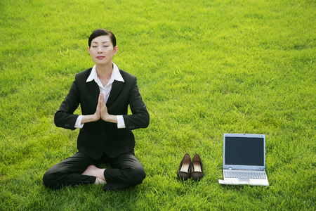 Businesswoman in lotus position beside shoes and laptop