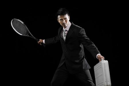 racquet: Businessman holding a briefcase and a tennis racquet