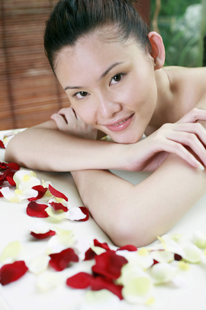 lying forward: Woman smiling at the camera while lying forward on massage table LANG_EVOIMAGES