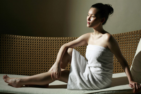 Woman in towel relaxing on couch