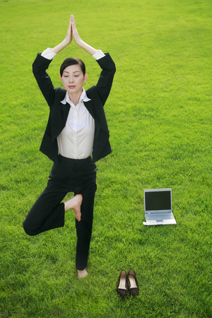 Businesswoman in yoga pose at the park