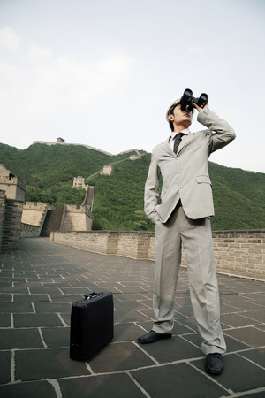 using binoculars: Businessman in safety helmet using binoculars