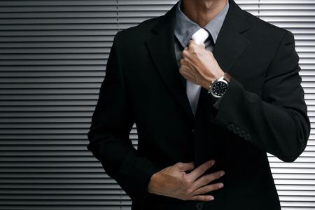 adjusting: Businessman adjusting his tie LANG_EVOIMAGES