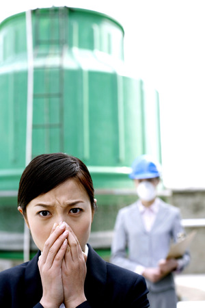 Businesswoman covering her nose, colleague in safety helmet and protection mask watching