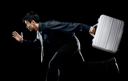 Businessman holding briefcase, getting ready to run LANG_EVOIMAGES