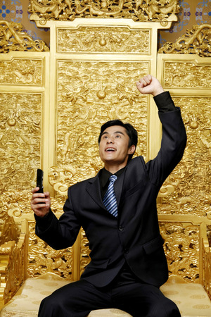 jubilating: Businessman jubilating while holding his mobile phone