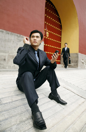 palmtop: Businessman using palmtop, man walking in the background