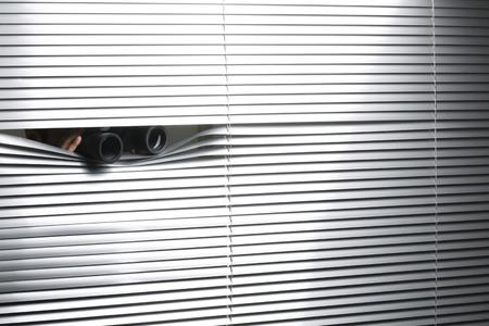 Peeping through the window blinds with binoculars Stockfoto