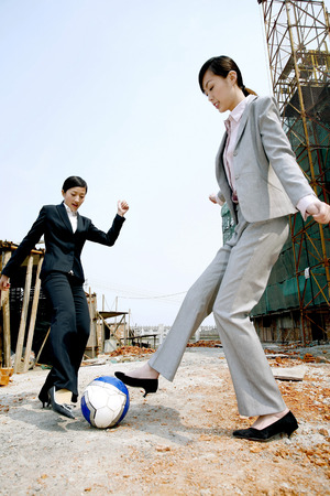 full grown: Businesswomen playing soccer at construction site