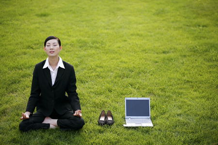 lotus position: Businesswoman in lotus position beside shoes and laptop