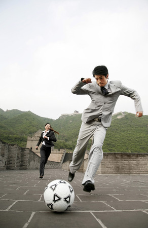 Businessman kicking football, businesswoman chasing from behind