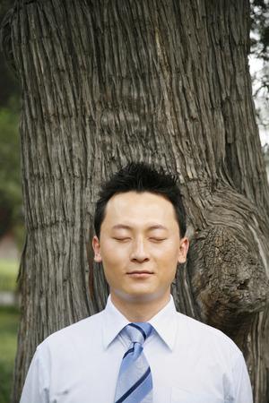 eyes closing: Businessman smiling while closing his eyes LANG_EVOIMAGES