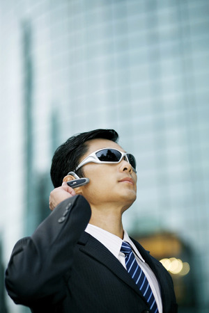 handsfree device: Businessman with sunglasses talking on hands-free device