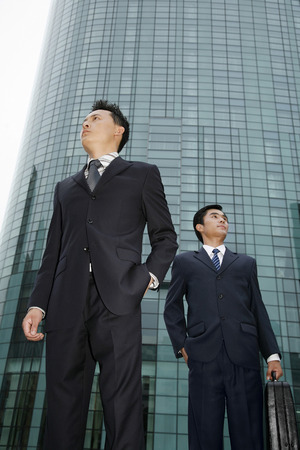 full grown: Businessmen standing with hands in pocket