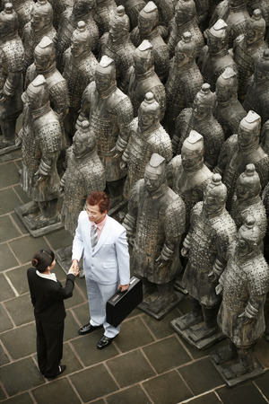 huang: Business people shaking hands beside terracotta soldiers