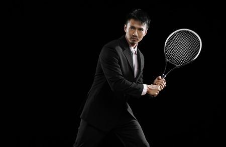 tennis racquet: Businessman striking a pose with a tennis racquet LANG_EVOIMAGES