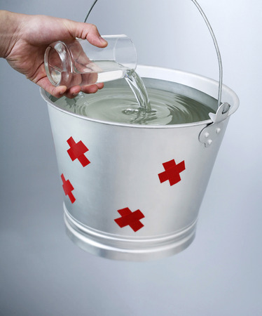 Hand pouring water from a glass into a pail