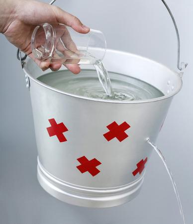 Colada de la mano agua de un vaso en una cubeta con fugas Foto de archivo - 39012344