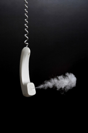 telephone receiver: Smoke coming out from hanging telephone receiver