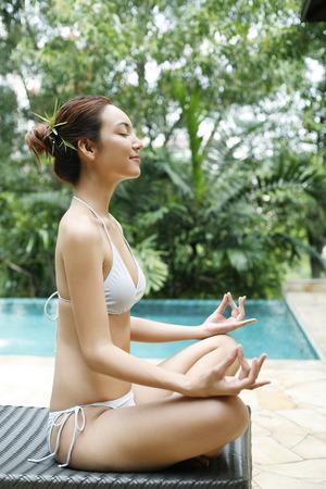 full grown: Woman in bikini meditating LANG_EVOIMAGES