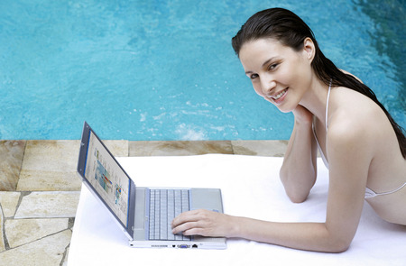 lying forward: Woman lying forward by the poolside using laptop LANG_EVOIMAGES