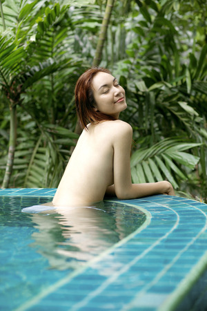 Topless woman resting at the side of swimming pool LANG_EVOIMAGES