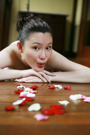 lying forward: Woman lying forward around flower petals, pouting lips