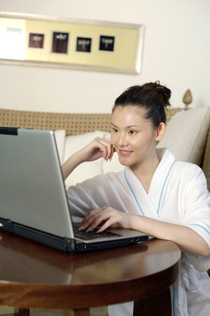 Woman in bathrobe typing on laptop LANG_EVOIMAGES
