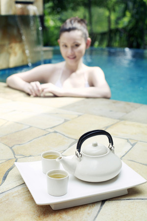teacups: Teapot and teacups on tray, woman posing on edge of swimming pool