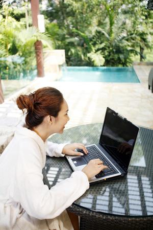 Woman in bathrobe using laptop