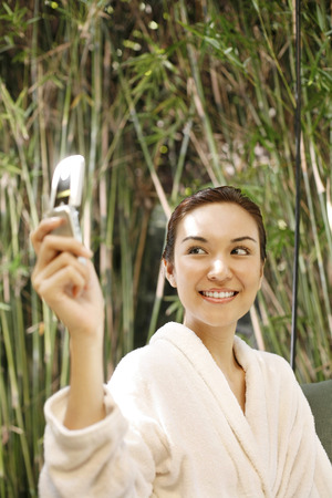Woman in bathrobe talking picture with mobile phone