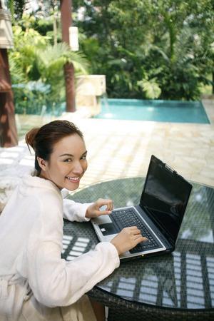 woman bathrobe: Woman in bathrobe using laptop
