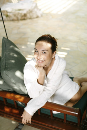 woman bathrobe: Woman in bathrobe relaxing on chair swing LANG_EVOIMAGES