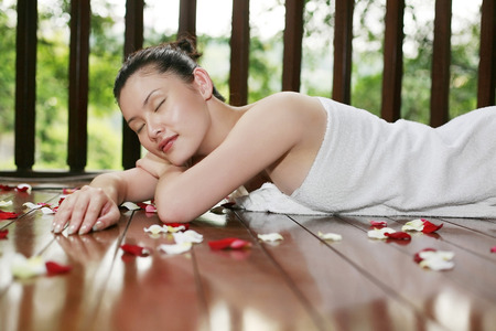 lying forward: Woman lying forward on wooden platform with scattered flower petals
