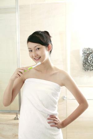 adult brushing teeth: Woman brushing teeth in the bathroom LANG_EVOIMAGES