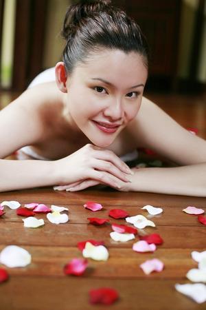 lying forward: Woman lying forward around flower petals, looking at camera