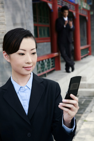 palmtop: Businesswoman text messaging on the mobile phone, businessman using palmtop in the background LANG_EVOIMAGES