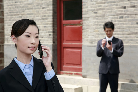 palmtop: Businesswoman talking on the mobile phone, businessman using palmtop in the background