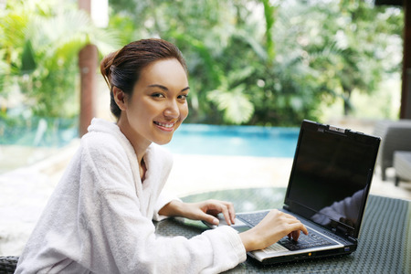 technology: Woman smiling at the camera while using laptop
