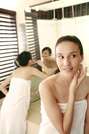 two persons only: Woman applying moisturizer on her face, friend brushing teeth in the background LANG_EVOIMAGES